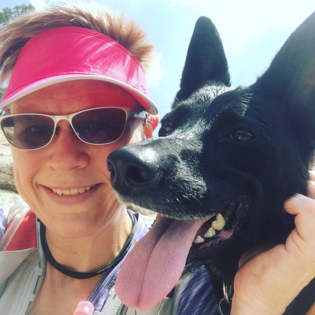 A photo of the author in running gear with her dog Nairobi, a black shepard mix with big pointy ears, shown panting.