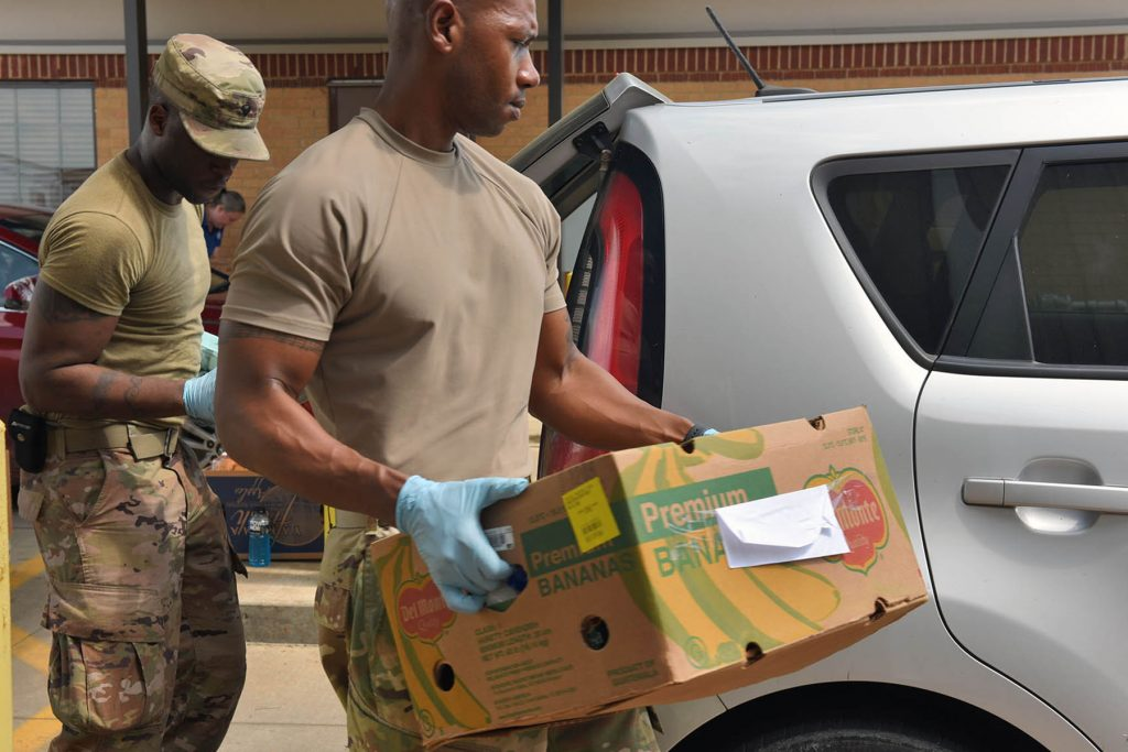 A Louisiana National Guard soldier on duty puts a box of food into the back of a white SUV at a food bank.