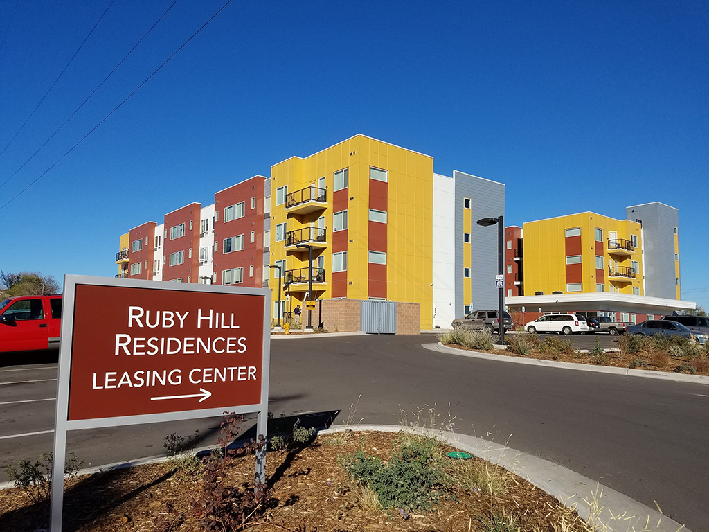 "Modern apartment building in brick red, mustard yellow, and grey blue.  Sign in foreground reads ""Ruby Hill Residences Leasing Center"" followed by an arrow."