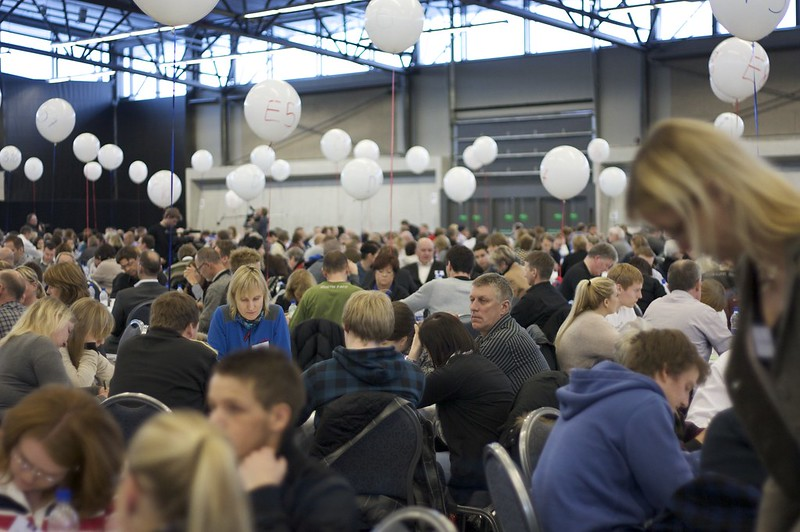 A very large conference room full of randomly selected members of the public is shown.  These citizens are helping to guide the future of Iceland.