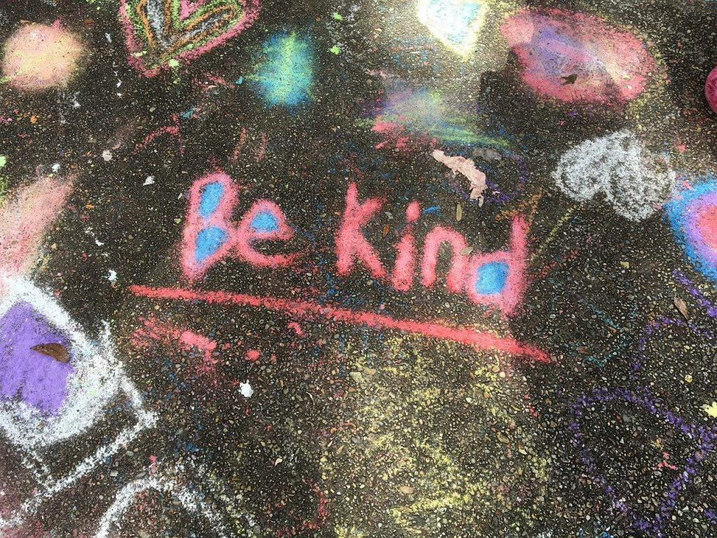 Be Kind written in sidewalk chalk.  Being members of a community, as found in civil society, can help us be kinder people.