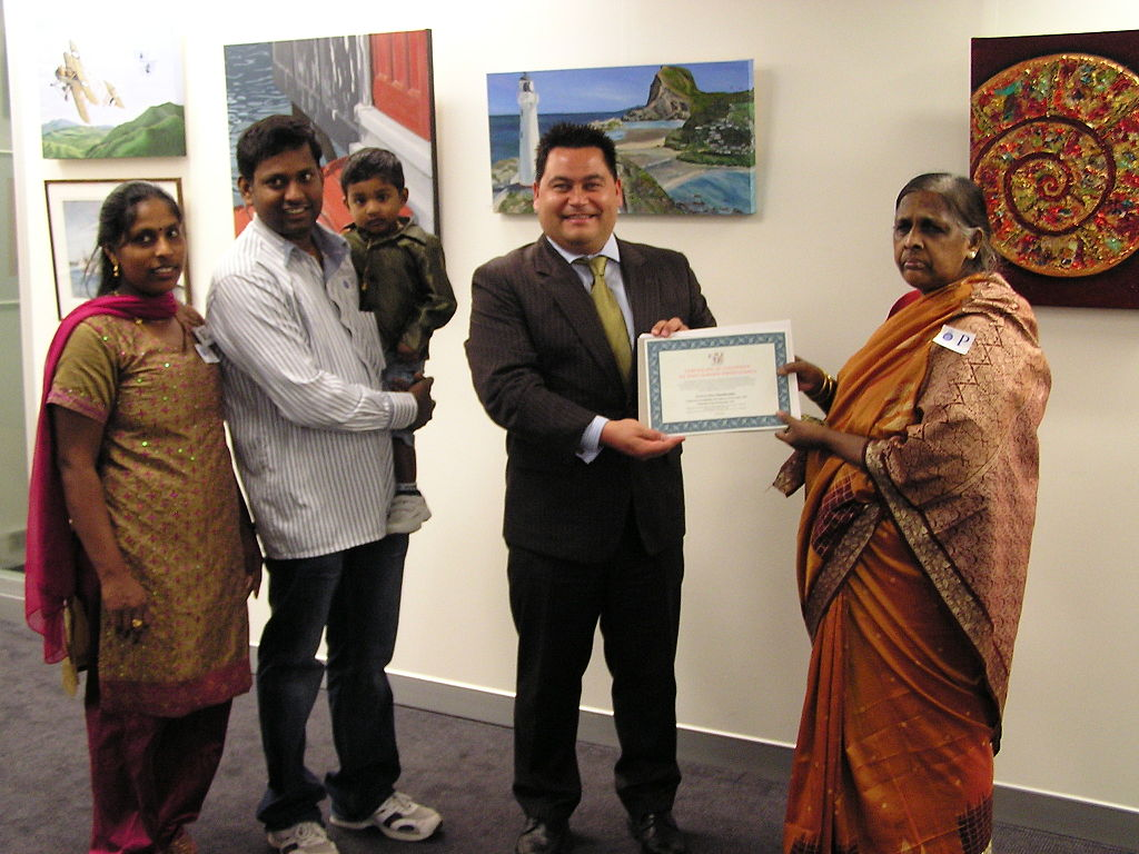 Immigrants whose clothing suggests a South Asian origin hold up a Citizenship Certificate.  People who have studied for the Citizenship Test typically know more about our democracy than native-born citizens.  We need to do a better job of educating ourselves if we want to foster a culture of democracy.