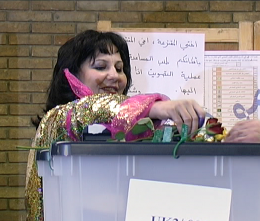 An Iraqi Kurdish woman in exile in London places a rose atop a ballot box after casting her vote.  We all need to be this excited about voting.